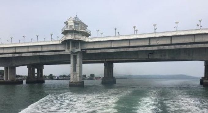 Un homme handicapé et une jeune fille saute du pont Sarasin au nord de Phuket