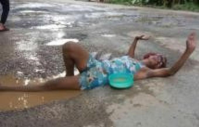 Un homme se baigne dans les nids de poule pour protester contre l'état des routes
