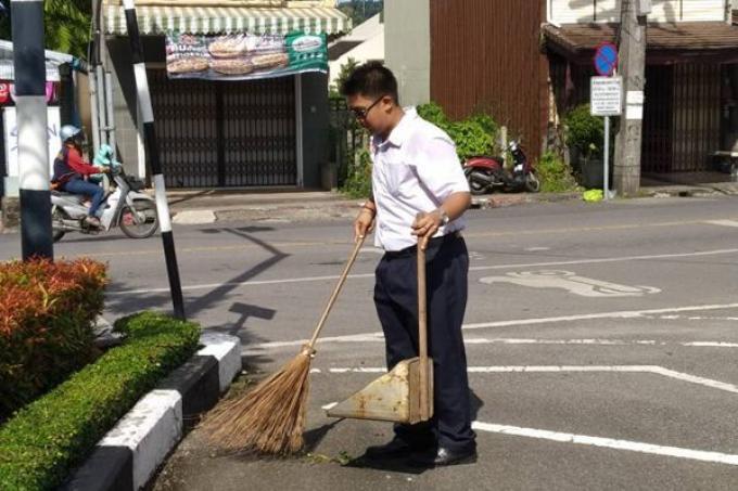 Il aide sa mère à nettoyer sa rue le matin avant l'école